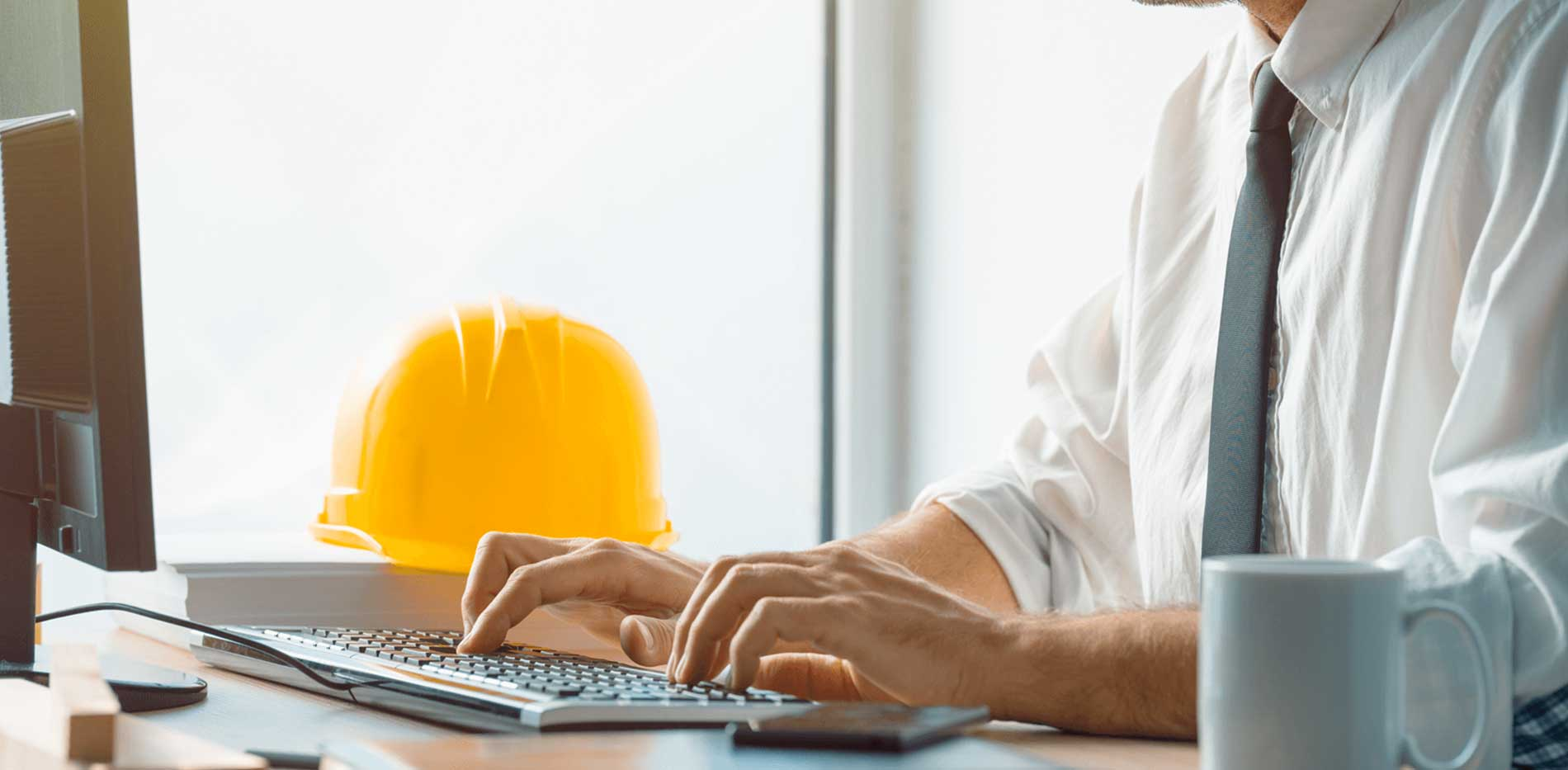 Man working at desk with hard hat next to him